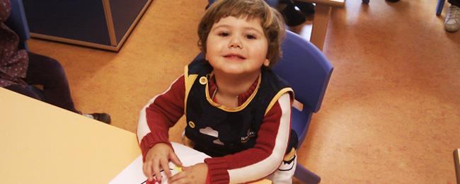 Niño con bata de la escuela mirando a la cámara