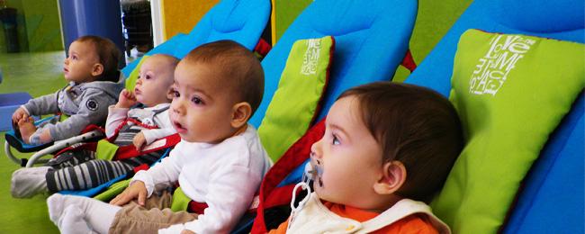 Primer plano de dos bebés sentados en sus hamacas