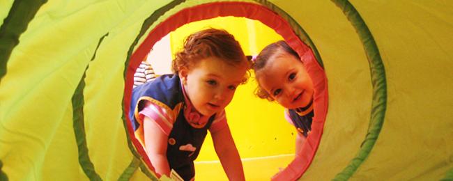 Dos niños entrando en un túnel de tela