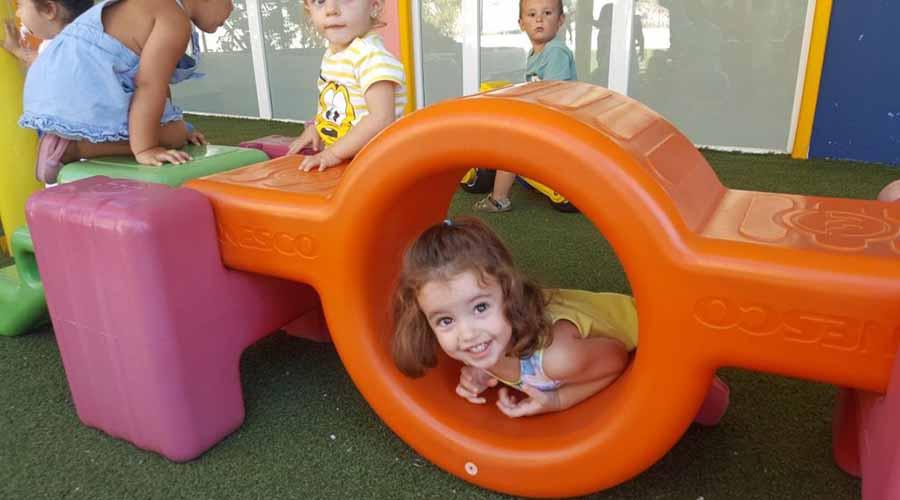 Niña de dos años jugando en un columpio naranja