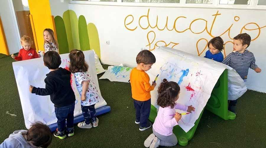 Niños en el patio pintando sobre una pizarra blanca