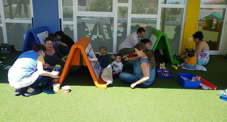 Padres y alumnos de infantil pintando en pizarras en el suelo