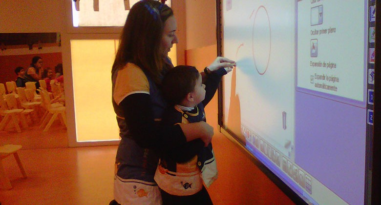 Profesora enseñando al alumno en una pizarra digital