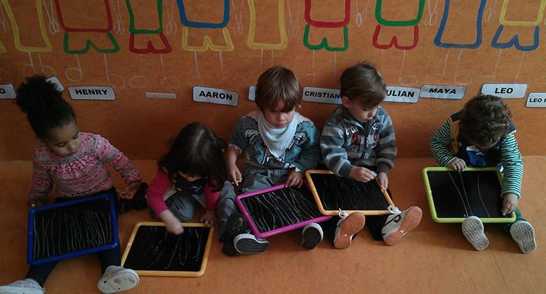 Niños y niñas de 1 año pintando en pizarras individuales