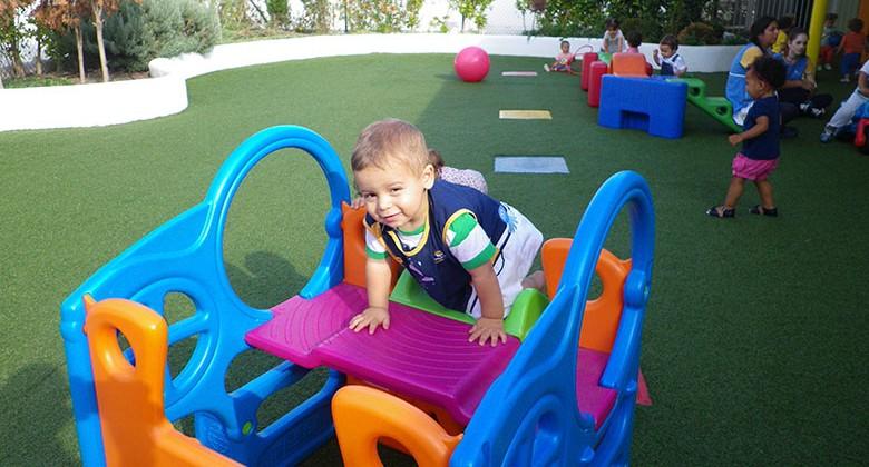 Niño de 1 año subiendo por un tobogán de colores