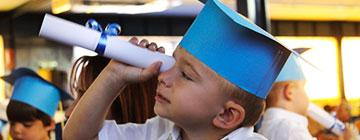 Niño con birrete mirando por un pergamino
